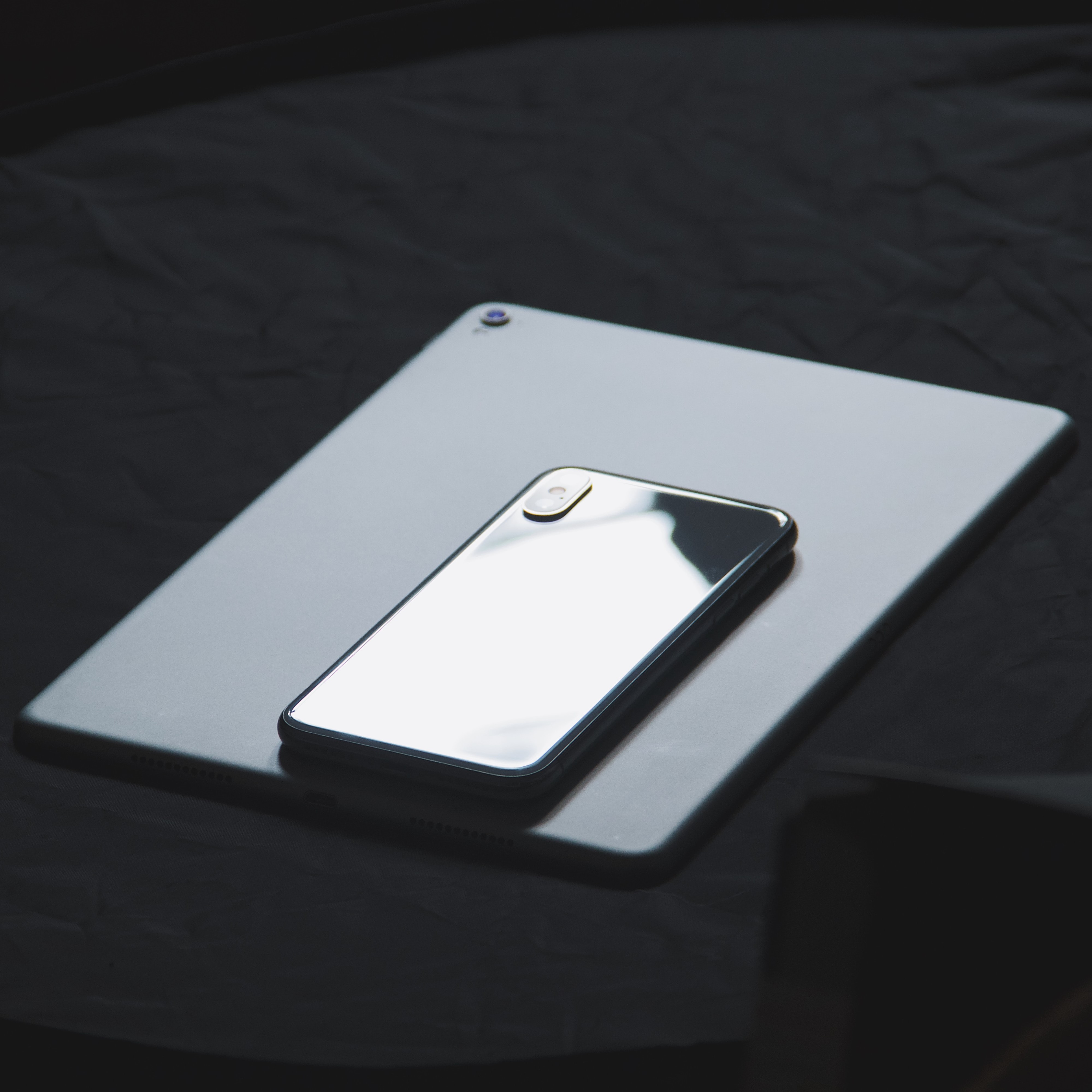 iPhone resting facedown on a facedown iPad