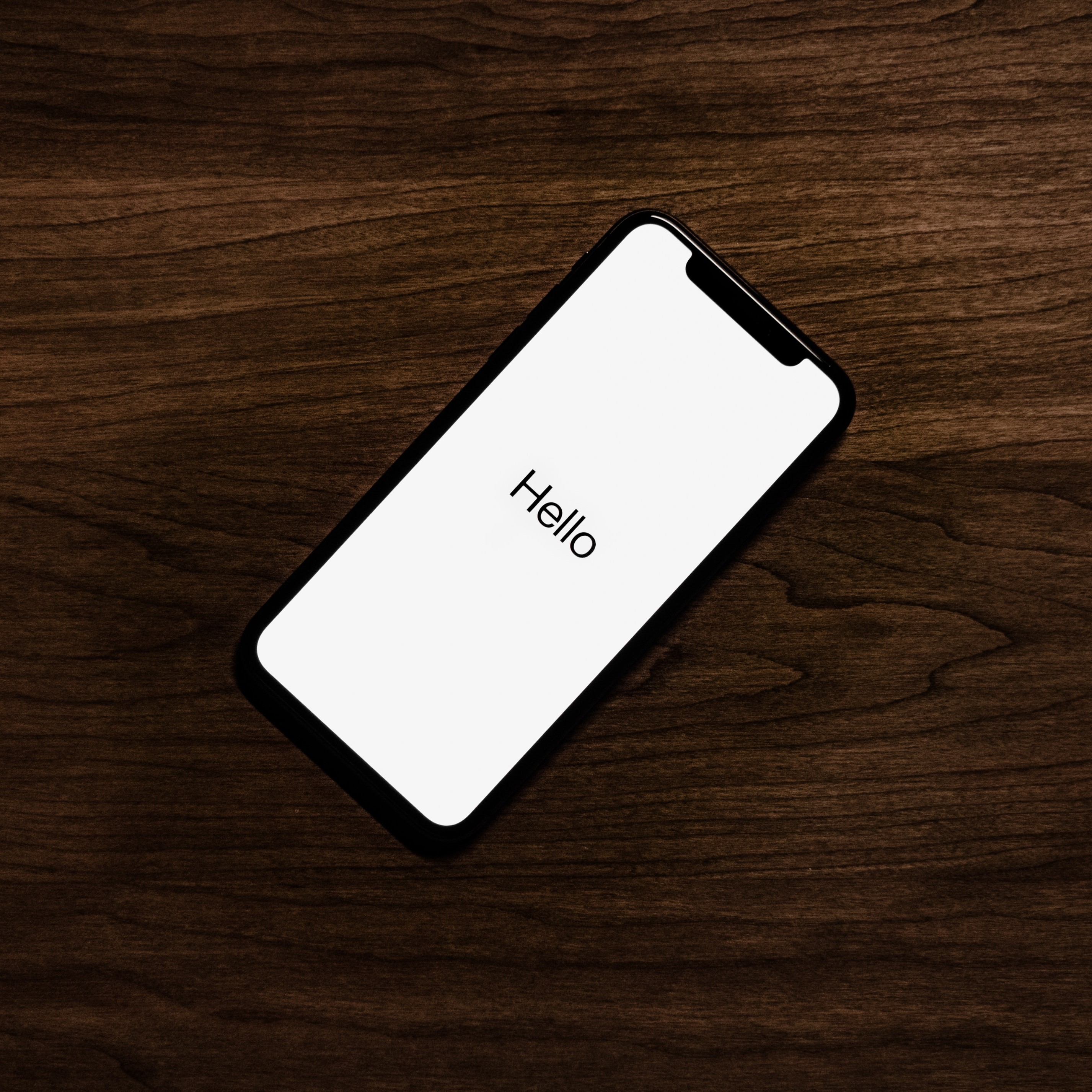 """iPhone X with """"Hello"""" displayed"""