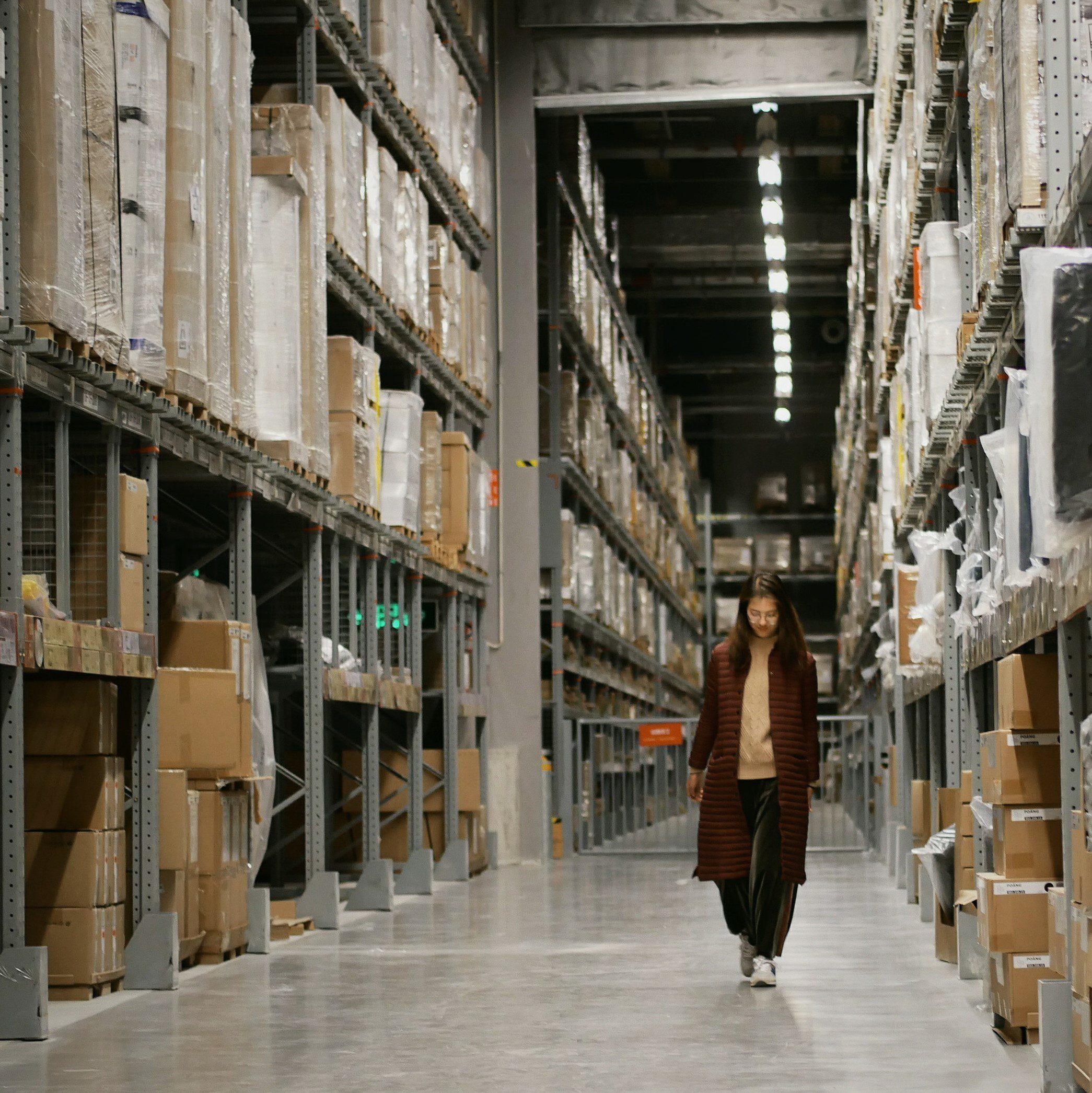 woman walking through an aisle of a warehouse