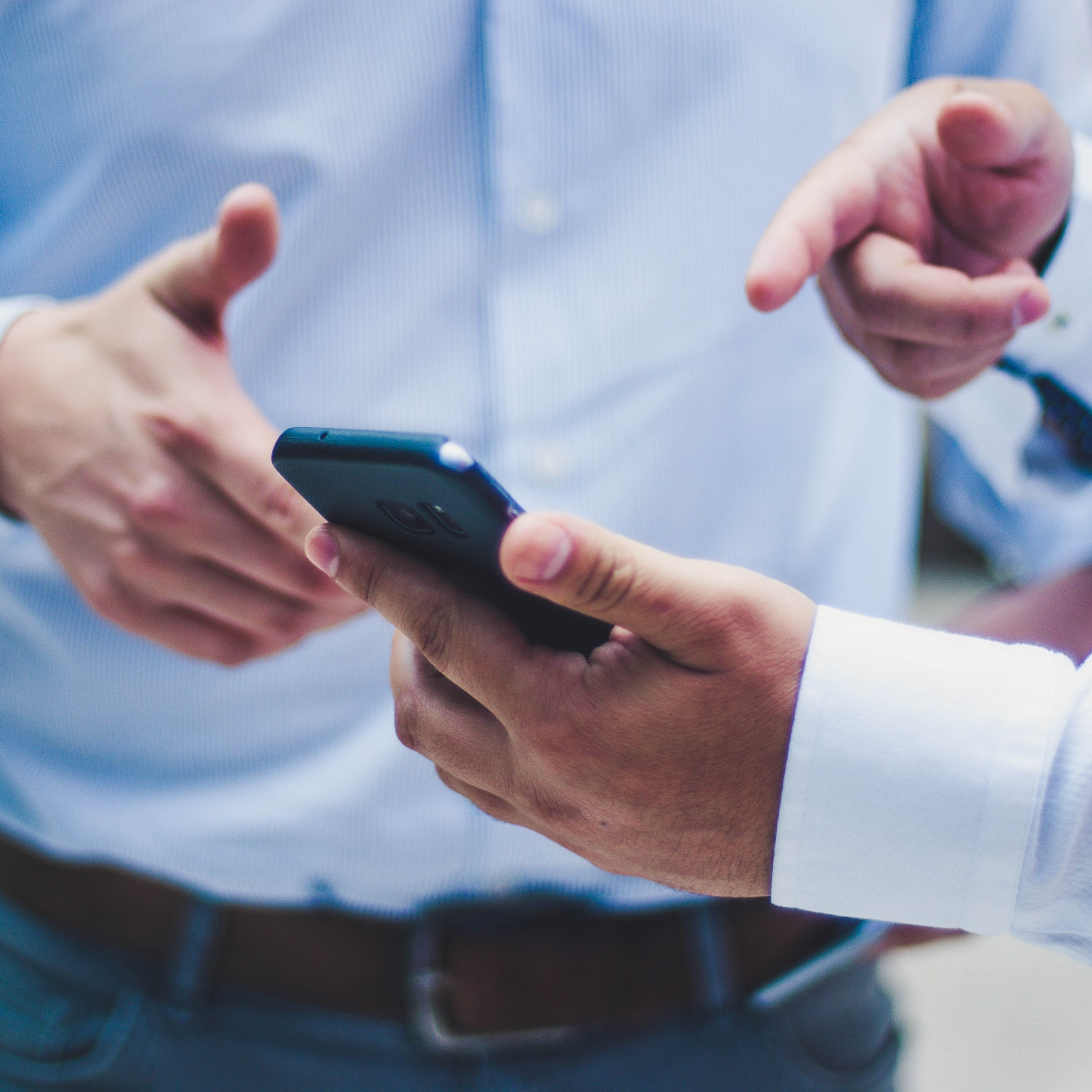 two men's hands pointing to a phone