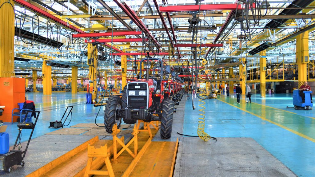 interior of industrial building with a line of tractors