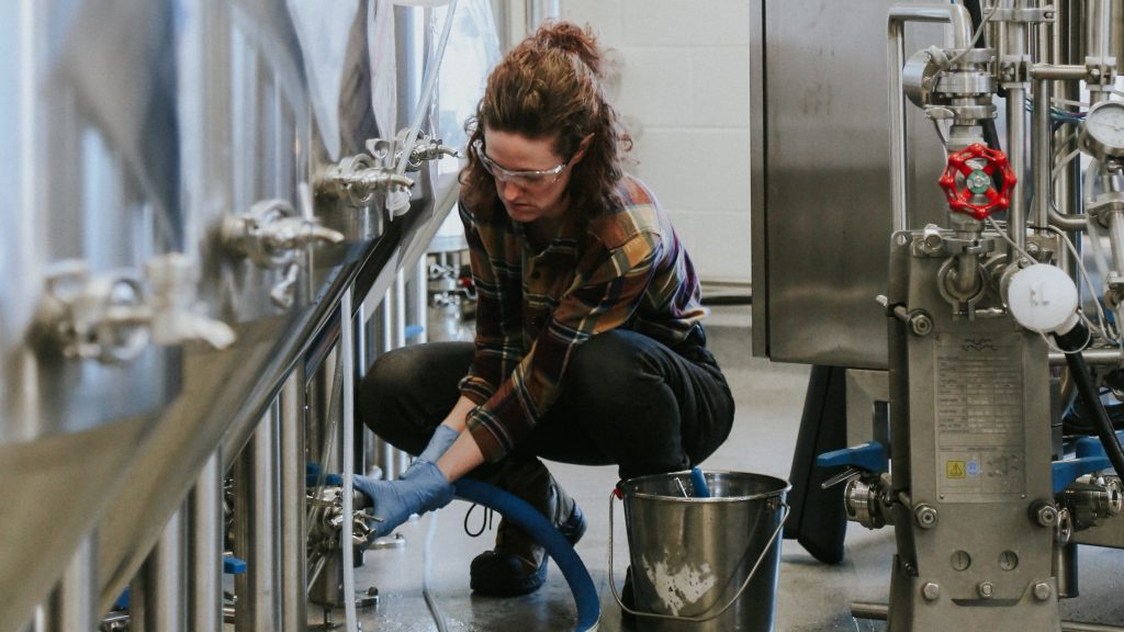 woman with safety glasses crouching next to equipment