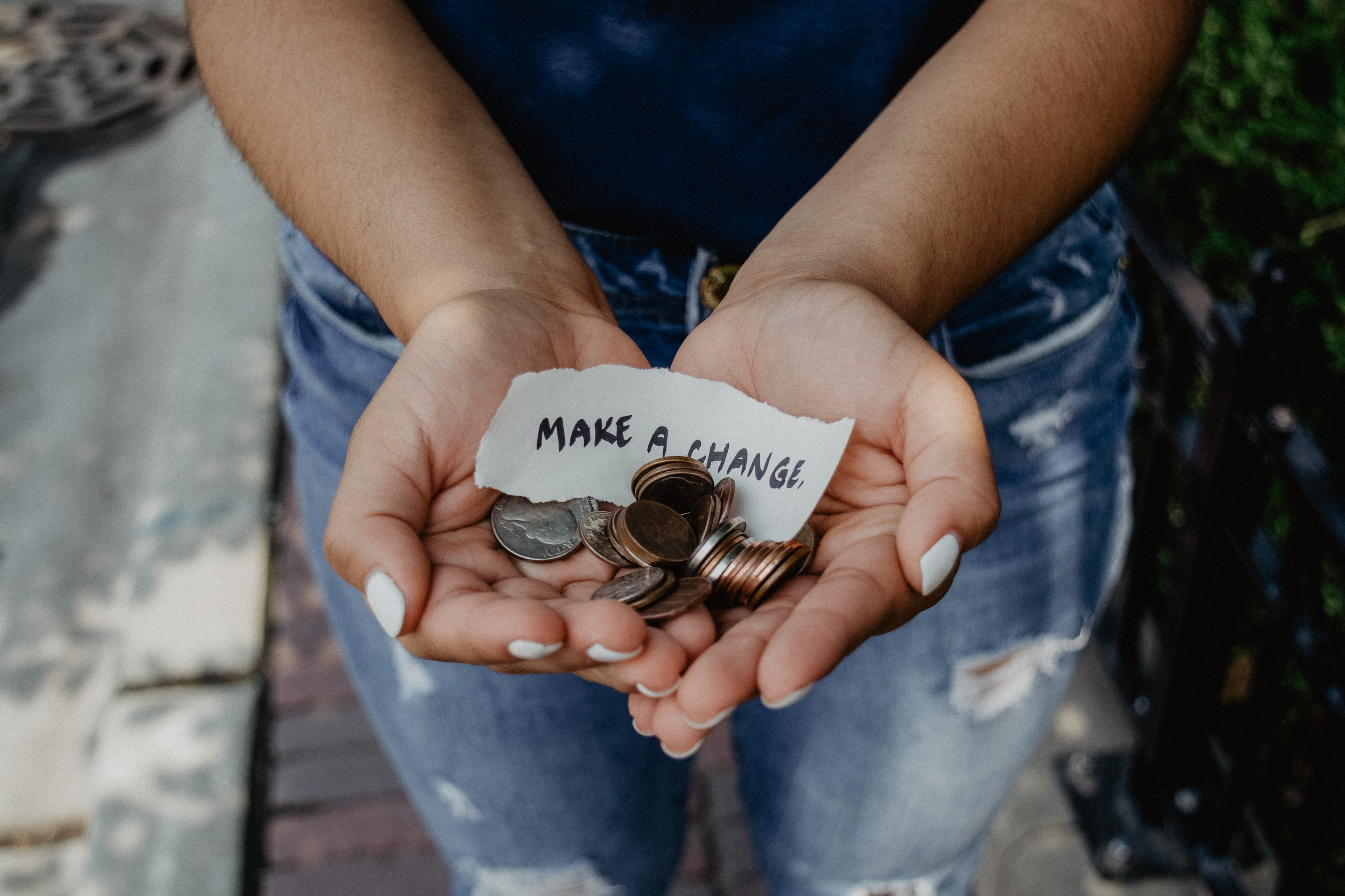 "hands holding coins and a slip of paper saying ""make a change"""