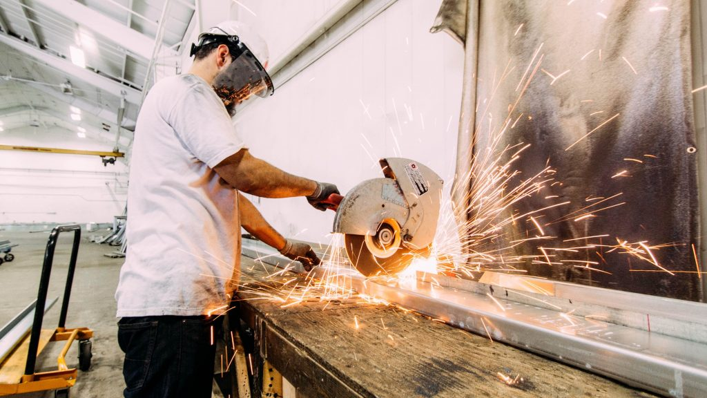 man wearing hard hat and mask with circular saw shooting sparks