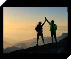 Hikers high five on a mountain summit